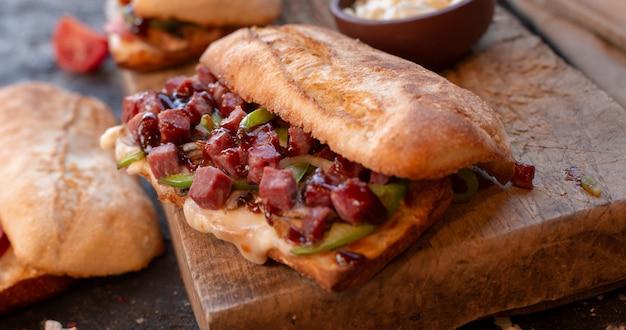 Большая порция сэндвича с багетом, полная смешанных колбас и овощей Бесплатные Фотографии
