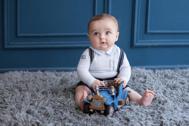 カーペットの上に座って、青い車で遊んで金髪の幼児。 無料写真