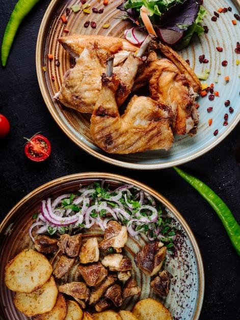 チキンのグリル、ビーフシチュー、ポテトチップス、玉ねぎとグリーンサラダのプレート。 無料写真