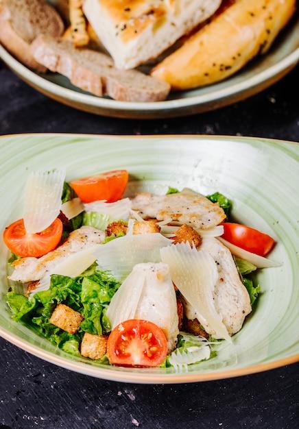 緑、トマト、刻んだパルメザンチーズのシーザーサラダ。 無料写真