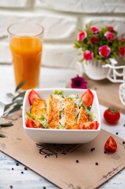 健康的なグリルチキンシーザーサラダ、チーズ、オレンジジュース、クルトン 無料写真