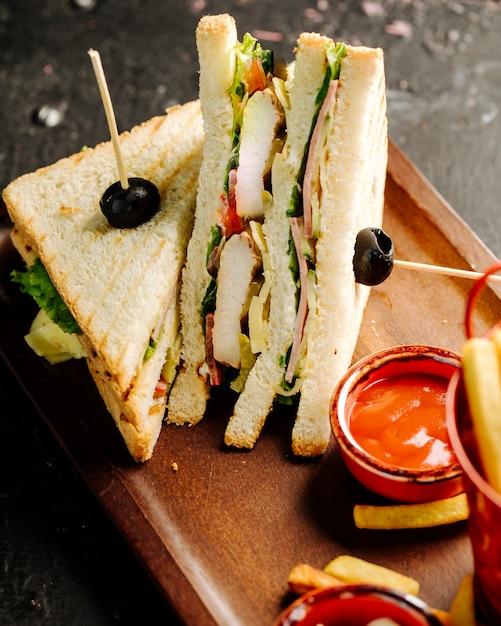 ホットチリソースとフライドポテトのクラブサンドイッチ。 無料写真