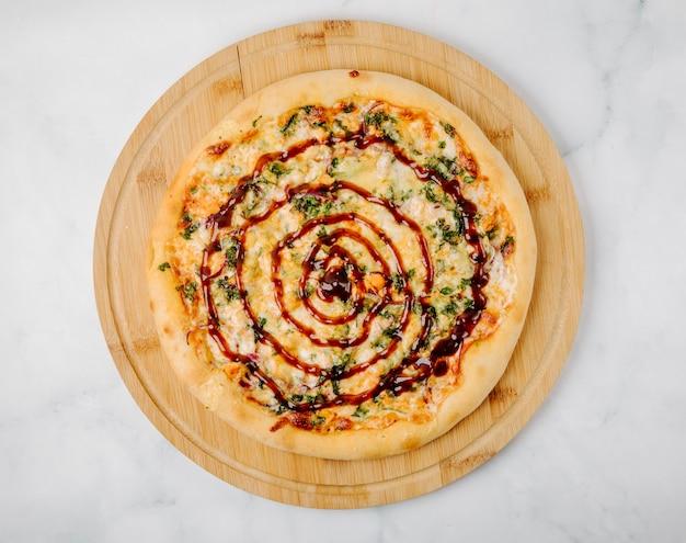 木製の大皿にハーブと赤いソースのピザ。 無料写真