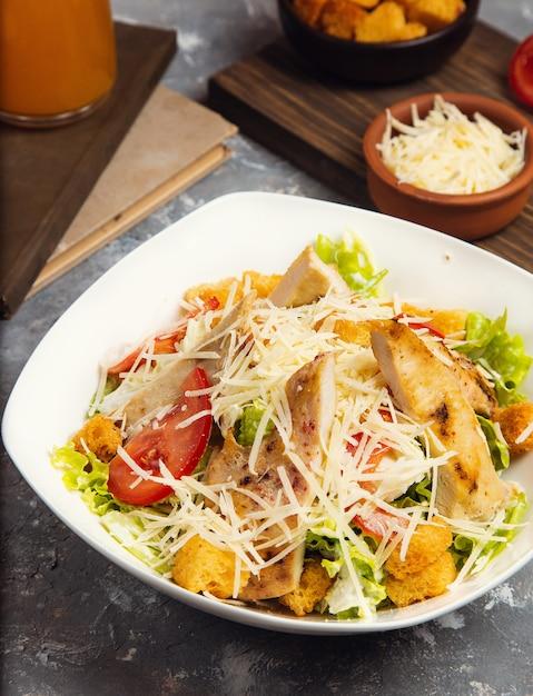 チキンサラダ。チキンシーザーサラダ。シーザーサラダのグリルチキンプレート。鶏胸肉のグリルとプレートのサラダ 無料写真