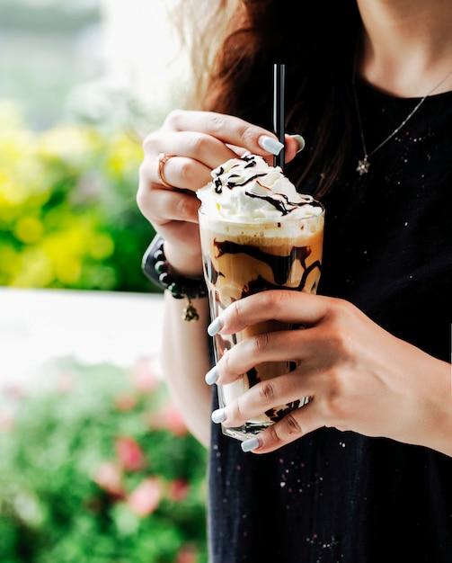チョコレートシロップとアイスクリームボールとコーヒーのスムージーのグラスを持つ女性。 無料写真