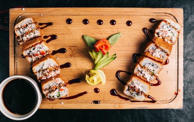 Суши роллы с соевым соусом на деревянной доске. Бесплатные Фотографии