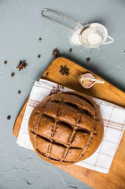 スパイスとテーブルの上のタオルの上のライ麦パン 無料写真