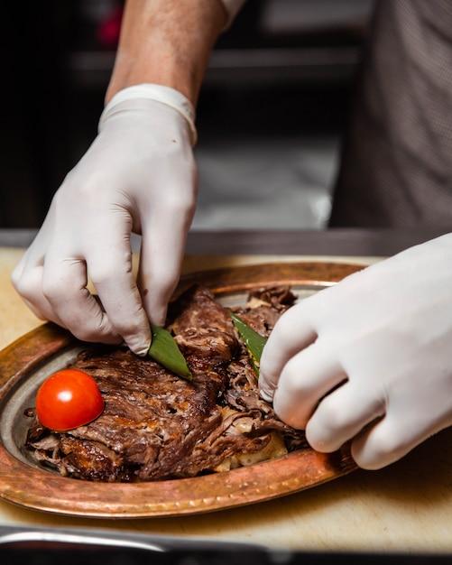 Шеф-повар готовит стейк блюдо и добавляет листья томата и орегано. Бесплатные Фотографии