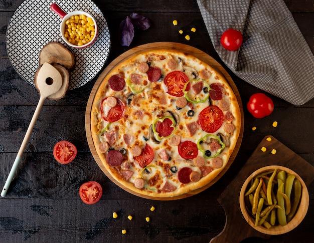 トマトのスライスとペパロニのピザ。 無料写真