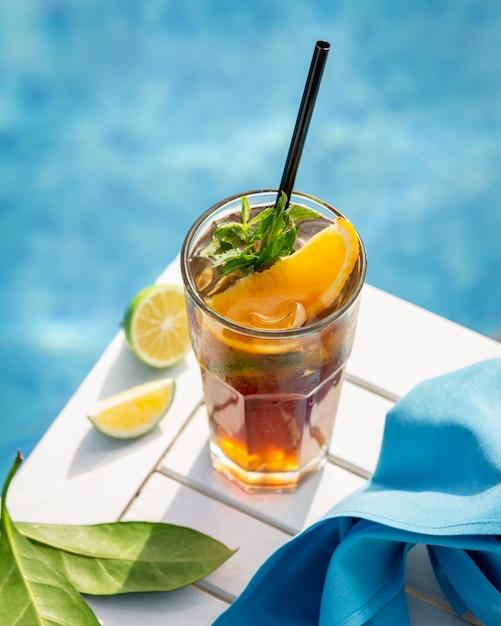 プールのそばにオレンジ、レモン、ミントの葉の黄色い飲み物。 無料写真