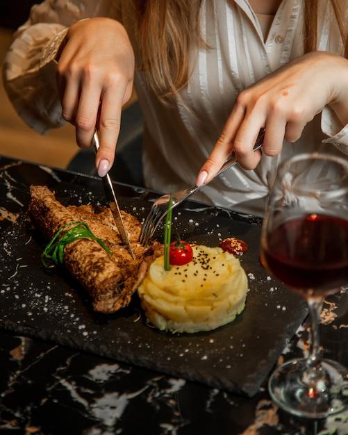 マスクジャガイモと赤ワインのグラスと女性カット肉ステーキ。 無料写真