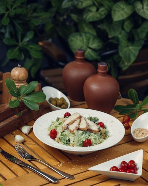 木製テーブルの上の白い皿の中の白身肉、レタス、チェリートマトのギリシャシーザーサラダ。 無料写真