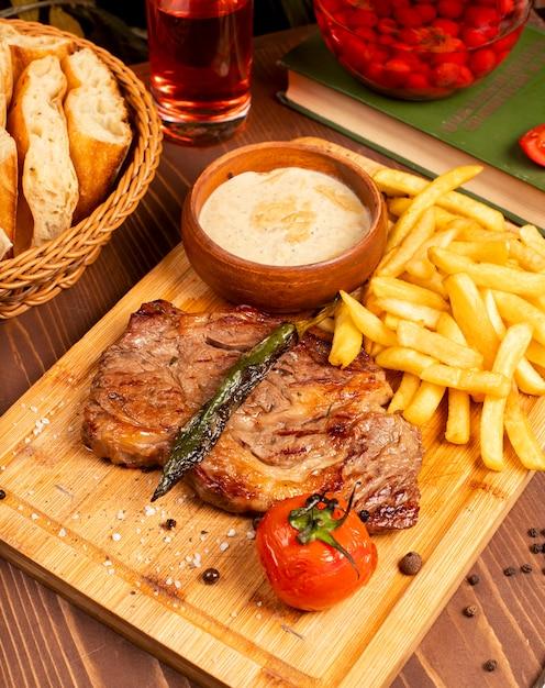 ビーフステーキ、フライドポテト、サワークリームマヨネーズソース、木の板にハーブ 無料写真