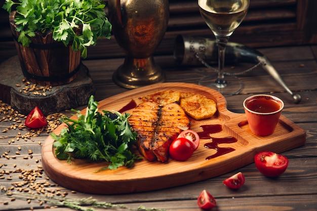魚の切り身のグリル、トマト、赤ソース、ハーブ、白ワインのグラス。 無料写真