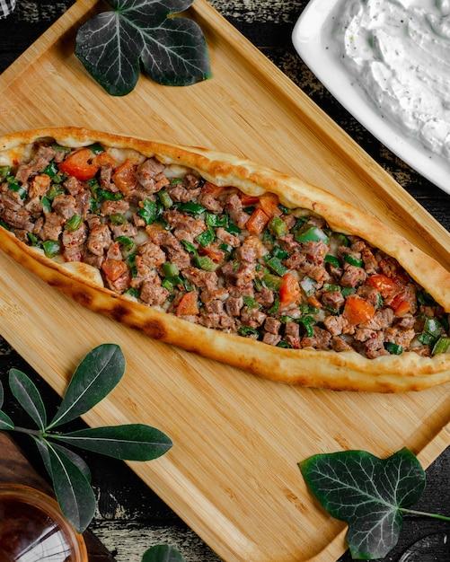 木製トレイの中に肉と野菜を詰めたトルコ風ピザ。 無料写真
