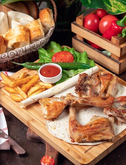 木の板にケチャップと野菜のラバッシュでフライドポテト焼き手羽先 無料写真