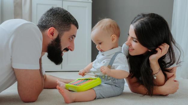 床で子供と遊ぶ親。 無料写真