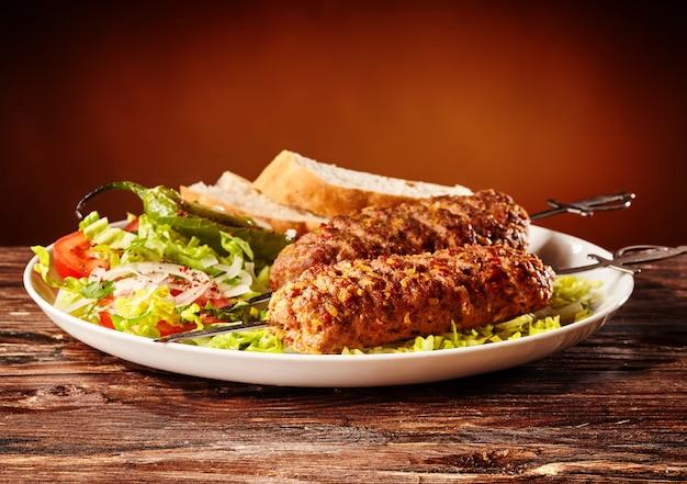 Шашлык кавказский, мясное шашлык с зеленым салатом и ломтики хлеба Бесплатные Фотографии
