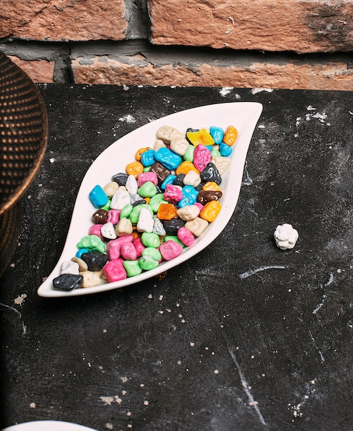 石レンガの白いプレートボウルの中の多色ボンボン菓子(ボールキャンディー) 無料写真