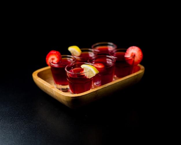 黒い空間の竹の盛り合わせの中にレモンとイチゴの小さなサングリアグラス。 無料写真