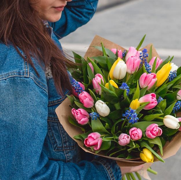 色とりどりのチューリップの花束とジーンズジャケットの女性。 無料写真