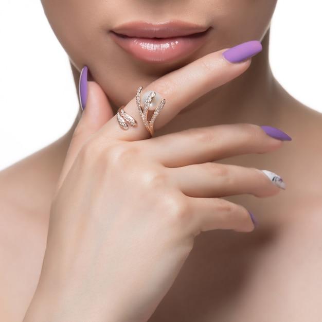 Женщина продвигая золотое кольцо дизайн в ее палец. Бесплатные Фотографии