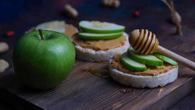 もちパンと青リンゴのスライスと蜂蜜入りのカリカリの天然ピーナッツバターサンドイッチ。 無料写真