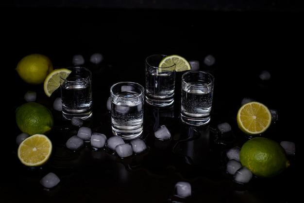 Алкогольные выстрелы с лаймом и кубиками льда на черном Бесплатные Фотографии