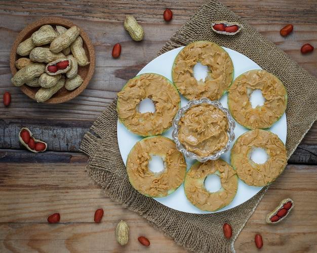 健康的なサンドイッチ。素朴なトップビューにピーナッツバターと赤スグリとピーカンナッツと青リンゴラウンド 無料写真