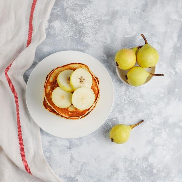 Домашний завтрак: блинчики по-американски с грушами и медом, чашка чая на бетоне. вид сверху и копия Бесплатные Фотографии