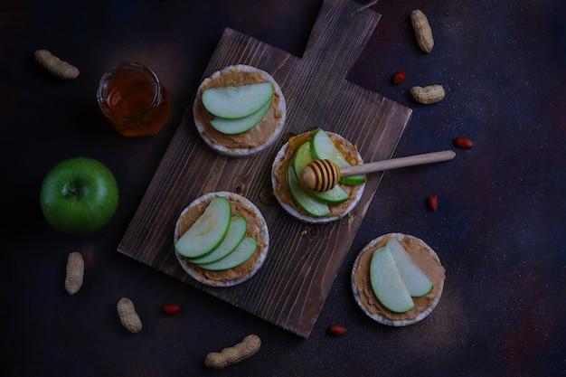 Хрустящий сэндвич с натуральным арахисовым маслом с рисовым хлебом, кусочками зеленого яблока и медом. Бесплатные Фотографии