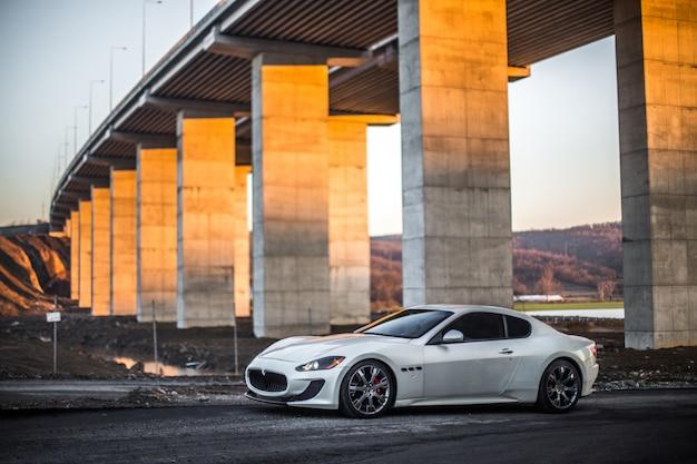 橋の下の白いクーペスポーツ車の駐車場。 無料写真