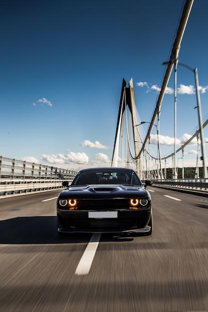 橋の上の黒いセダンのスポーツカーの正面図。 無料写真