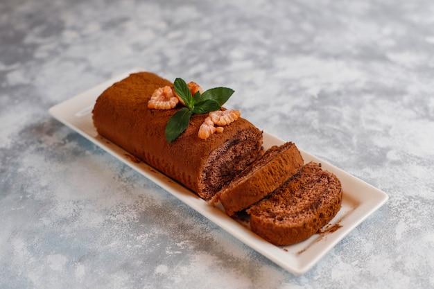 Шоколадный торт рулет с какао-порошком на белой тарелке, вид сверху Бесплатные Фотографии