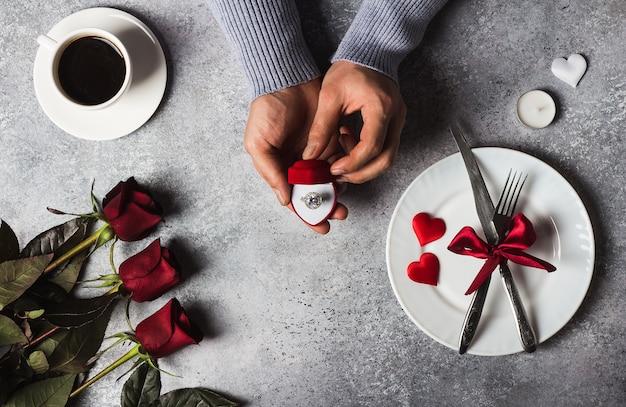 バレンタインの日ロマンチックなディナーテーブルセッティング婚約指輪を持つ男の手 無料写真