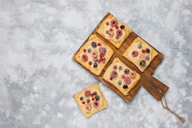 Свежее вкусное слоеное тесто со сладкими ягодами на бетоне Бесплатные Фотографии