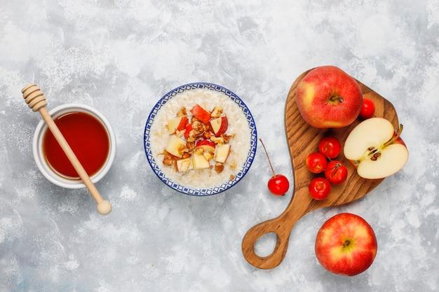 蜂蜜と赤いリンゴのスライス、トップビューでボウルにオートミールのお 無料写真