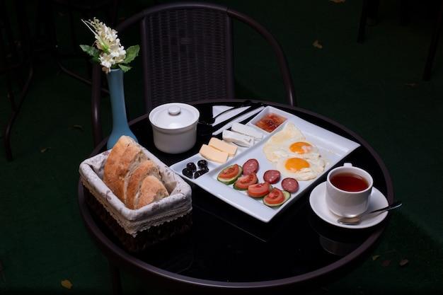目玉焼き、ソーセージ、チーズ、ジャム、バター、パン、お茶の入った朝食トレイ。 無料写真