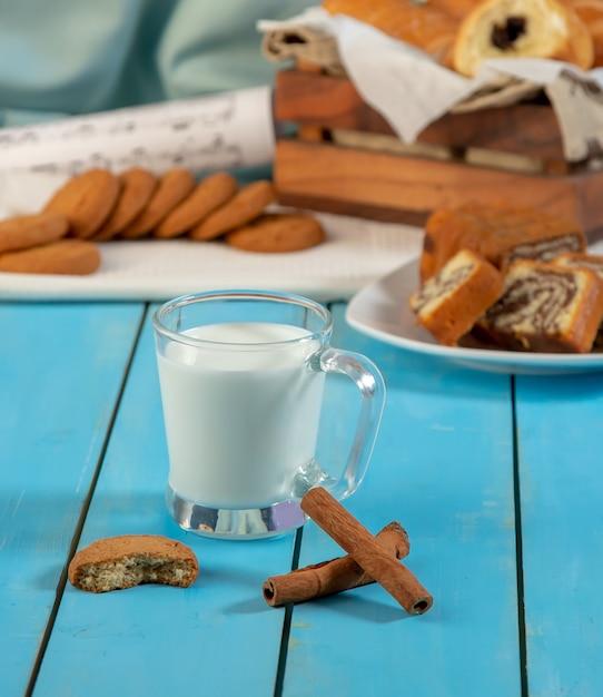 シナモンスティックとクッキーが入ったミルクカップ。 無料写真