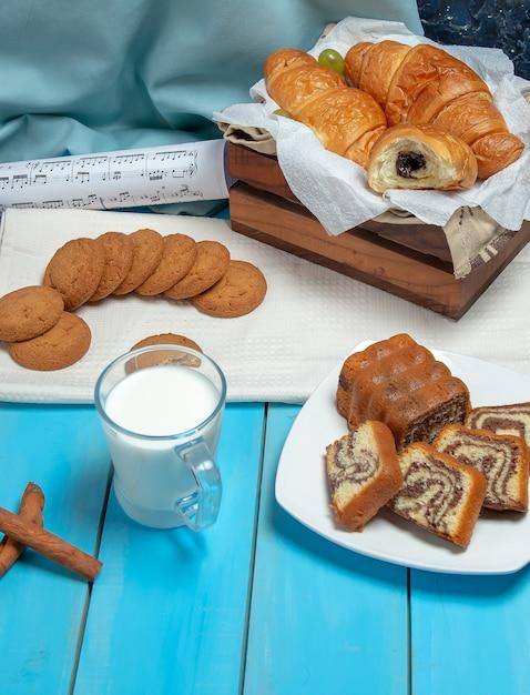 テーブルの上のシナモンスティックとペストリーと牛乳のカップ。 無料写真