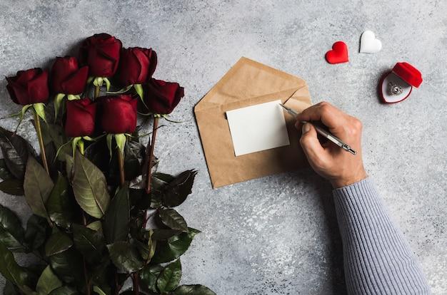 グリーティングカードとラブレターを書くペンを持つバレンタインデー男の手 無料写真