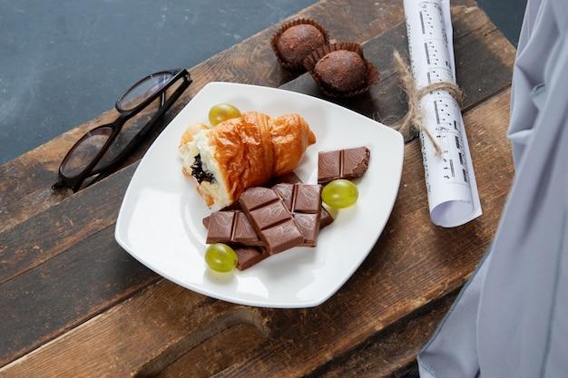 Кусок круассана и шоколада в белой тарелке на деревянной доске Бесплатные Фотографии