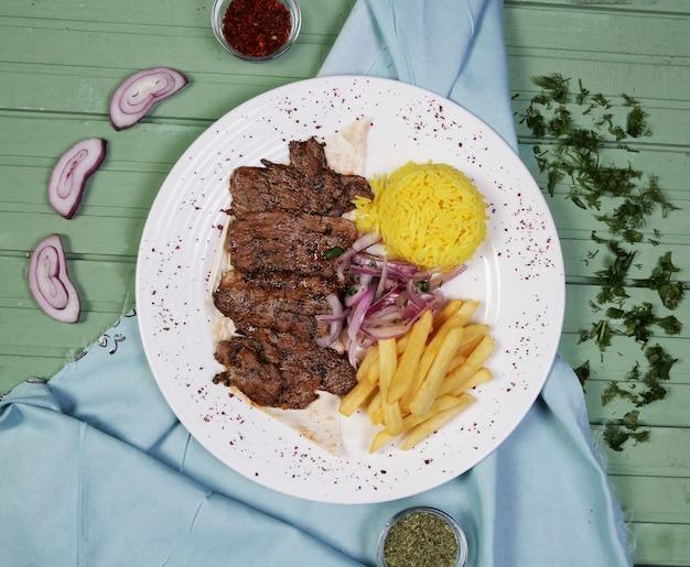 白い皿の中のフライドポテトとライスの付け合わせの肉ステーキ 無料写真
