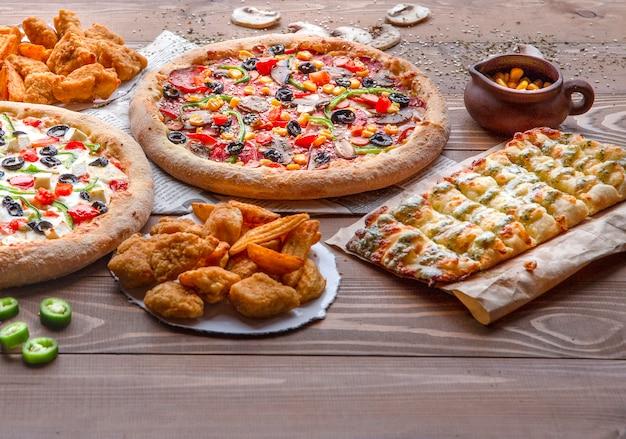 Пицца, куриное барбекю, жареный картофель и сырные рулетики на деревянном столе Бесплатные Фотографии