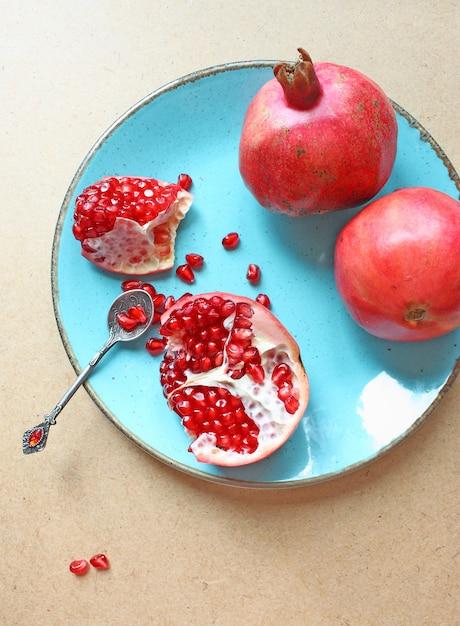 青いプレートの赤いザクロ 無料写真
