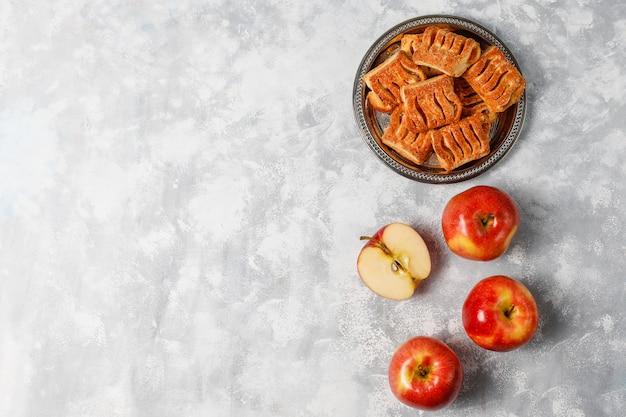 アップルジャムと軽いコンクリートの新鮮な赤いリンゴで満たされたパイ生地のクッキー 無料写真