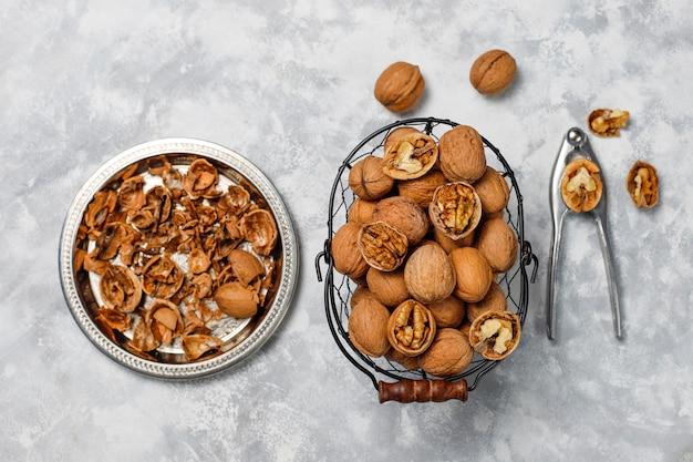 Целые грецкие орехи в скорлупе в пищевой металлической корзине, ядра грецких орехов. вид сверху на бетон Бесплатные Фотографии