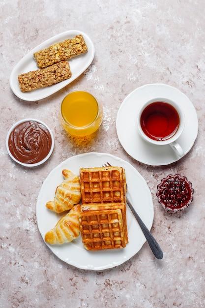 コーヒー、オレンジジュース、ワッフル、クロワッサン、ジャム、ナッツペーストの光、トップビューで美味しい朝食 無料写真