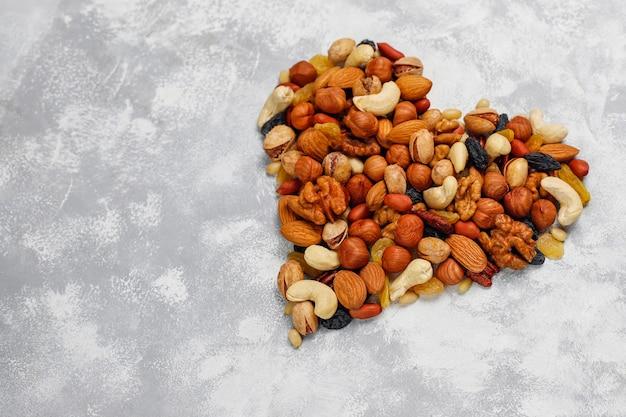 ハートの形のナッツの品揃えカシューナッツ、ヘーゼルナッツ、クルミ、ピスタチオ、ピーカンナッツ、松の実、ピーナッツ、レーズン。トップビュー 無料写真