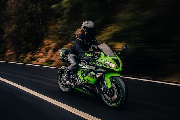 道路で緑のバイクを運転します。 無料写真